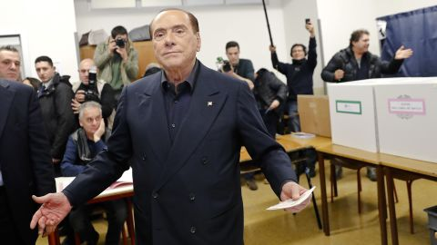 Italian former premier and leader of Forza Italia (Let's Go Italy) party Silvio Berlusconi listens to reporters at a polling station in Milan, Italy, Sunday, March 4, 2018. More than 46 million Italians were voting Sunday in a general election that is being closely watched to determine if Italy would succumb to the populist, anti-establishment and far-right sentiment that has swept through much of Europe in recent years. (AP Photo/Antonio Calanni)