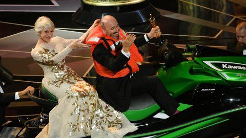 Helen Mirren with Oscar-winning costume designer Mark Bridges sitting on a Jet Ski, which he received as a prize for shortest acceptance speech.