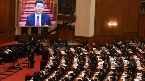 A live image of Chinese President Xi Jinping is seen on a screen above delegates as they listen to Premier Li Keqiang's speech during the opening session of the National People's Congress in the Great Hall of the People in Beijing on March 5, 2018.