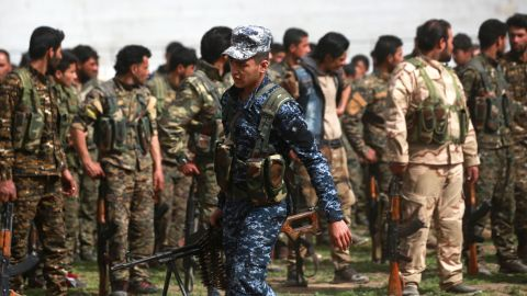 Members of the Syrian Democratic Forces gather to listen to an announcement from their commander in Raqqa on March 6, 2018.