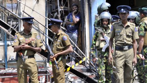 A man looks out from a burnt out home as Sri Lankan police commandos patrol on the streets of Pallekele, a suburb of Kandy, on March 6, 2018, following anti-Muslim riots that has prompted the government to declare a state of emergency. Sri Lanka on March 6 declared a nationwide state of emergency to quell anti-Muslim riots that have killed at least two people and damaged dozens of mosques and homes. The curfew in the district was extended after the body of a Muslim man was pulled from the ashes of a burnt building, threatening to further raise communal tensions that have flared up across Sri Lanka in recent weeks.  / AFP PHOTO / -        (Photo credit should read -/AFP/Getty Images)