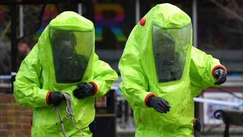 Members of the emergency services in green biohazard suits work to afix the tent over the bench where Sergei Skripal and his daughter Yulia were found.