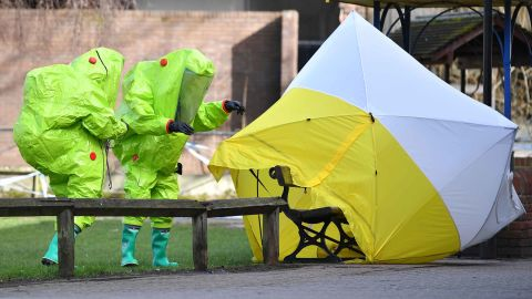 Members of the emergency services in green biohazard suits place a tent over the city center bench where the Skripals were found collapsed on March 4.