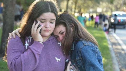 """TOPSHOT - Students react following a shooting at Marjory Stoneman Douglas High School in Parkland, Florida, a city about 50 miles (80 kilometers) north of Miami on February 14, 2018.A gunman opened fire at the Florida high school, an incident that officials said caused """"numerous fatalities"""" and left terrified students huddled in their classrooms, texting friends and family for help.The Broward County Sheriff's Office said a suspect was in custody. / AFP PHOTO / Michele Eve Sandberg        (Photo credit should read MICHELE EVE SANDBERG/AFP/Getty Images)"""
