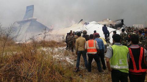Rescuers survey the plane's smoking debris.