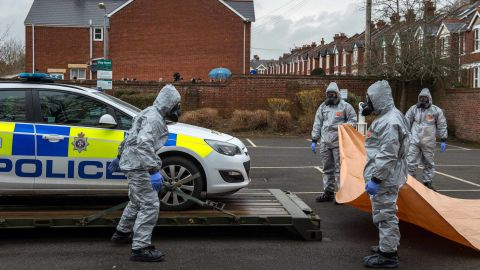 Military personnel wearing protective suits remove a police car and other vehicles from a public park park as they continue investigations.