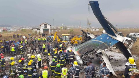 """Emergency personnel work around the wreckage of a plane that crashed while landing at the Tribhuvan Airport in Kathmandu, Nepal, on Monday, March 12. Flight BS 211, which was flying in from Dhaka, Bangladesh, <a href=""""https://www.cnn.com/2018/03/12/asia/kathmandu-plane-crash/index.html"""" target=""""_blank"""">crashed and burst into flames</a> after approaching the runway from the wrong direction, officials said. Dozens were killed."""