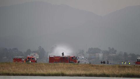 Fire trucks work to extinguish the plane's smoldering wreckage.