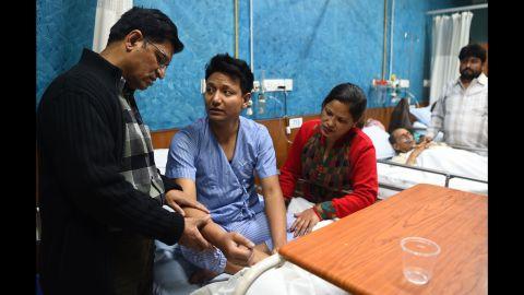 Plane crash survivor Sanam Shakya, center, talks with his parents at a hospital in Kathmandu.