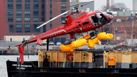 A helicopter is hoisted by crane from the East River onto a barge, Monday, March 12, 2018, in New York. All five passengers aboard a helicopter that crashed into New York City's East River were confirmed dead early Monday morning by a NYPD spokesman. The pilot was able to escape the Sunday night crash after the aircraft flipped upside down in the water, officials said. (AP Photo/Mark Lennihan)