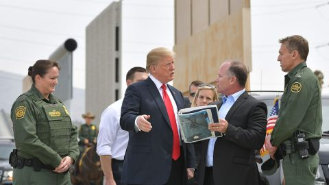 US President Donald Trump (C) is shown border wall prototypes in San Diego, California on March 13, 2018. / AFP PHOTO / MANDEL NGAN        (Photo credit should read MANDEL NGAN/AFP/Getty Images)