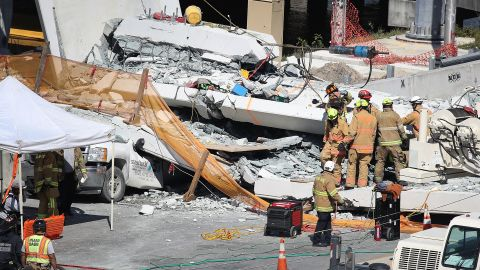 MIAMI, FL - MARCH 15:  Miami-Dade Fire Rescue Department personel and other rescue units work at the scene where a pedestrian bridge collapsed a few days after it was built over southwest 8th street allowing people to bypass the busy street to reach Florida International University on March 15, 2018 in Miami, Florida. Reports indicate that there are an unknown number of fatalities as a result of the collapse, which crushed at least five cars.  (Photo by Joe Raedle/Getty Images)