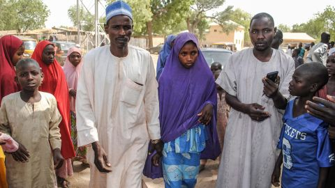 A girl released by Boko Haram walks with her father (L) in Dapchi on March 21, 2018.  Boko Haram Islamists who kidnapped 110 schoolgirls in Dapchi, northeast Nigeria, just over a month ago have so far returned 101 of the students to the town, the government said today. / AFP PHOTO / -        (Photo credit should read -/AFP/Getty Images)