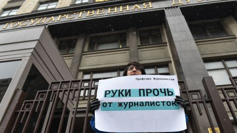 """A woman protesting outside the State Duma building in Moscow on Wednesday holds a placard reading """"hands off from female journalists."""""""