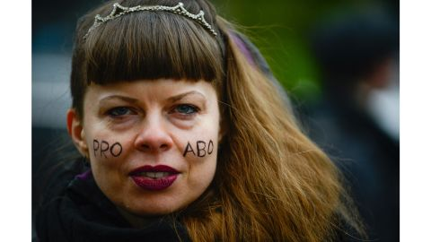 """A woman with """"Pro Abo"""" face paint attends a protest against a proposed  law to tighten abortion in Warsaw."""