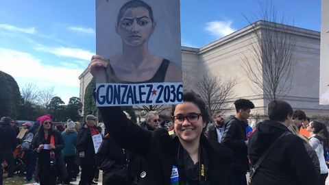 Becky Quiroga in Washington holds the poster she painted.