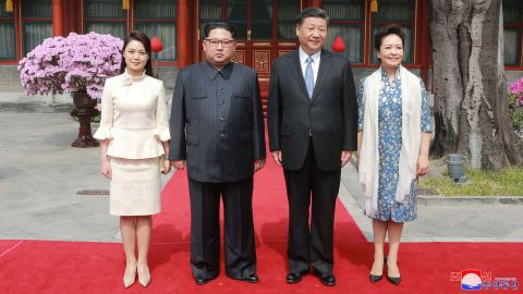 """In this March 27, 2018, photo, North Korean leader Kim Jong Un, center left, and his wife Ri Sol Ju, left, Chinese counterpart Xi Jinping, center right, and his wife Peng Liyuan pose for a photo at Diaoyutai State Guesthouse in Beijing. North Korea's leader Kim Jong Un and his Chinese counterpart Xi Jinping sought to portray strong ties between the long-time allies despite a recent chill as both countries on Wednesday, March 28, 2018,  confirmed Kim's secret trip to Beijing this week.  The content of this image is as provided and cannot be independently verified. Korean language watermark on image as provided by source reads: """"KCNA"""" which is the abbreviation for Korean Central News Agency.  (Korean Central News Agency/Korea News Service via AP)"""