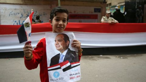 A boy holds a poster of Egyptian President Sisi on the last day of voting.