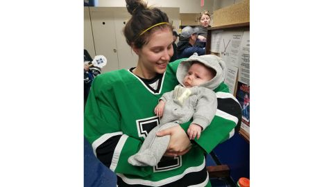 Serah Small holds her 8-week old baby, Ellie, while wearing her hockey uniform.