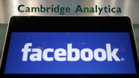 A laptop showing the Facebook logo is held alongside a Cambridge Analytica sign at the entrance to the building housing the offices of Cambridge Analytica, in central London on March 21, 2018.