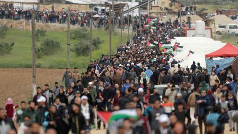 Palestinians march past a tent city erected along the border with Israel east of Gaza City on Friday.