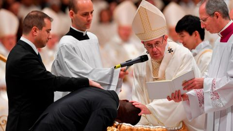 Pope Francis baptizes migrant John Ogah during Saturday's Easter service at the Vatican.