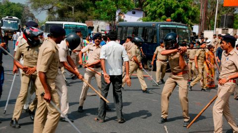 India's lower caste Dalit man stands as policemen beat him during a nationwide strike in Ahmadabad, India, Monday, April 2, 2018.  (AP Photo/Ajit Solanki)