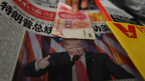 TOPSHOT - A vendor picks up a 100 yuan note above a newspaper featuring a photo of US president-elect Donald Trump, at a news stand in Beijing on November 10, 2016. The world's second-largest economy is US president-elect Donald Trump's designated bogeyman, threatening it on the campaign trail with tariffs for stealing American jobs, but analysts say US protectionism could create opportunities for Beijing. / AFP / GREG BAKER        (Photo credit should read GREG BAKER/AFP/Getty Images)