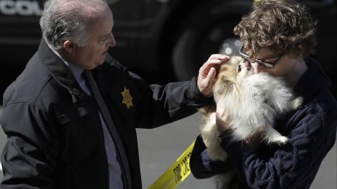 Burlingame Police Chief Eric Wollman hands a dog named Kimba to a man who didn't give his name but said he worked for YouTube.
