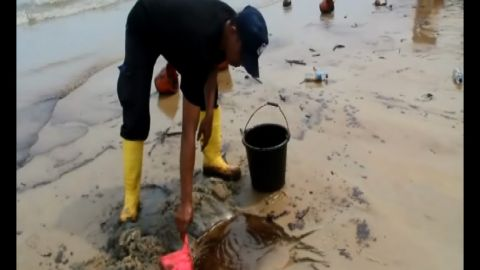 A worker collects oil from a beach following a spill in Balikpapan, East Kalimantan, Indonesia in this screengrab from CNN affiliate CNN Indonesia.