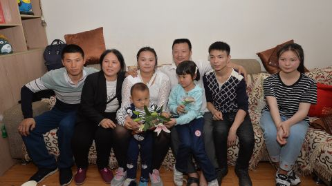 The families of Wang Mingqing and his missing daughter Kang Ying, second left, pose for photos after reuniting.