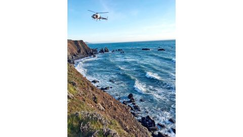 A helicopter hovers over a Mendocino County cliff where an SUV was discovered March 26.