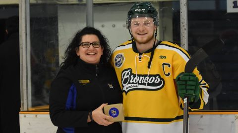 Logan Schatz, right, receives the player of the month award for February.