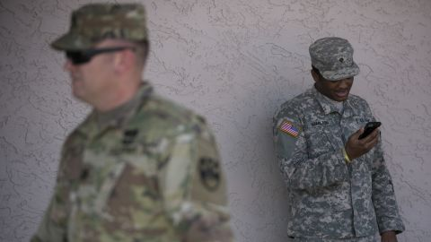 """A member of the Arizona National Guard talks on the phone on April 9, 2018 at the Papago Park Military Reservation in Phoenix.Arizona deployed its first 225 National Guard members to the Mexican border on Monday after President Donald Trump ordered thousands of troops to the frontier region to combat drug trafficking and illegal immigration. """"The Arizona National Guard will deploy 225 members of the Guard today to support border security measures,"""" the state militia said in a statement. / AFP PHOTO / Caitlin O'Hara        (Photo credit should read CAITLIN O'HARA/AFP/Getty Images)"""