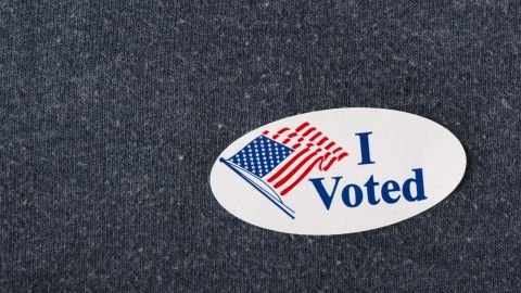 """Royalty-free stock photo ID: 415632082  Closeup of an American """"I voted"""" sticker placed on a navy shirt."""