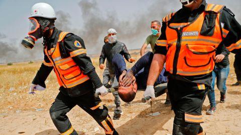 Palestinian paramedics evacuate an injured protester on April 13, 2018.
