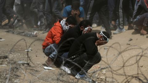 Palestinian protesters cover their faces against teargas during a protest at the Gaza-Israel border.