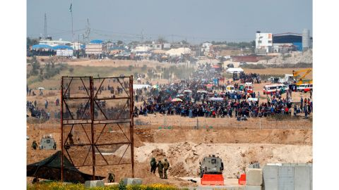 Israeli soldiers stand as Palestinian protesters gather along the Gaza-Israel border fence on Friday.
