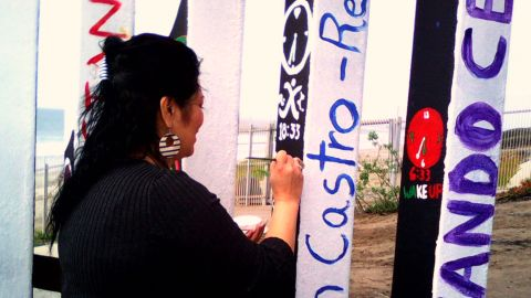 A volunteer paints names on the reverse side of the flag.