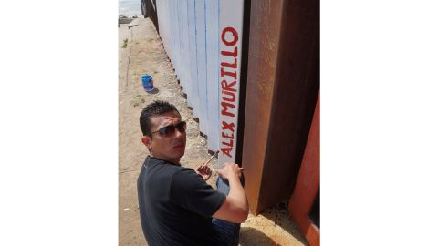 Alex Murillo, a deported US Navy veteran from Phoenix, paints his name on the upside down flag mural in Tijuana. Murillo was deported in 2012 after a drug conviction.