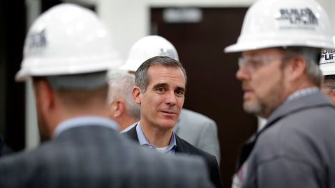 Los Angeles Mayor Eric Garcetti, center, visits with staff during a tour of a carpenters training facility on Friday, April 13, 2018, in Altoona, Iowa.