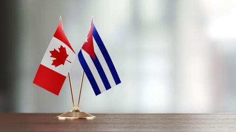 Cuban and Canadian flag pair on desk over defocused background. Horizontal composition with copy space and selective focus.