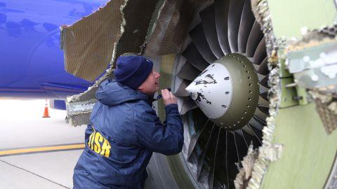 A National Transportation Safety Board investigator examines the damaged engine.