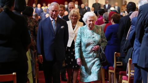 Queen Elizabeth II and Prince Charles arrive for the formal opening of the Commonwealth Heads of Government Meeting at Buckingham Palace in London on Thursday.