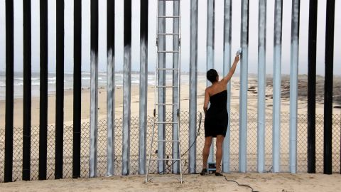 """Mexican-born artist Ana Teresa Fernandez created her mural """"Erasing the Border"""" in 2011 by painting sections of the fence the same color as the sky, creating the illusion that it is missing."""