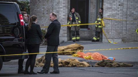 A coroner waits near the sidewalk where victims lie covered.