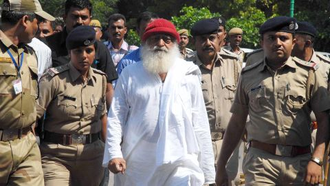 (FILES) In this file photo taken on October 14, 2013 Indian spiritual guru Asaram Bapu (C), accused of sexually assaulting a minor, is escorted by Gujarat state police in Jodhpur.An Indian guru with millions of followers is in court in Jodhpur on April 25, 2018 accused of raping a teenage devotee on the pretext of ridding her of evil spirits. / AFP PHOTO / --/AFP/Getty Images