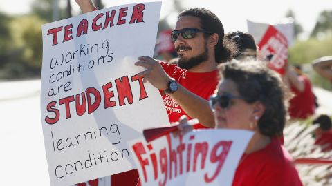 Teachers, parents and students line up along a local street waving to passing vehicles for the latest teacher protest for higher teacher pay and school funding Wednesday, April 25, 2018, in Phoenix. Teachers are scheduled to go on strike Thursday. (AP Photo/Ross D. Franklin)