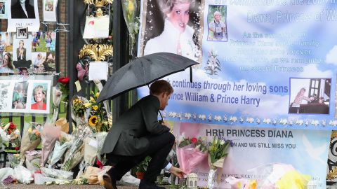 Prince Harry looks at flowers, photos and other souvenirs left as a tribute to Diana near the Sunken Garden at Kensington Palace in August 2017.