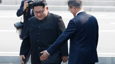 North Korean leader Kim Jong Un, left, crosses the border upon meeting with South Korean President Moon Jae-in, right, for the summit Friday.